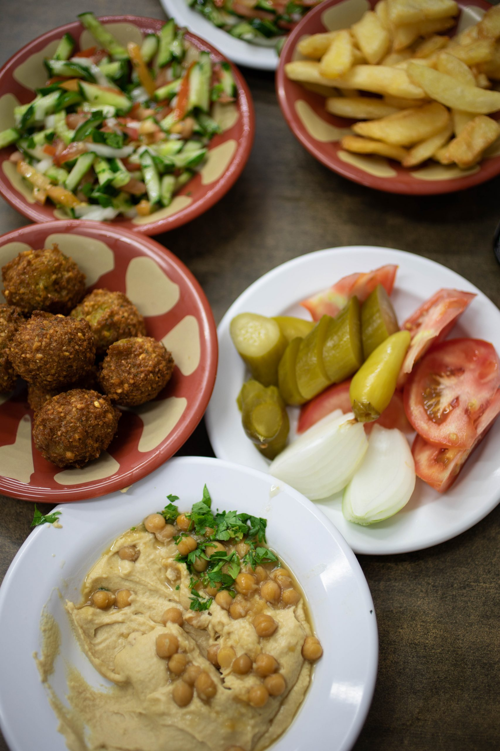 A falafel dish, and hummus dish with cheek peas, vegetables, pickles and vegetables as side dishes.